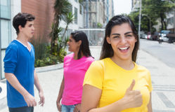 Beautiful latin woman with yellow shirt and friends in the city Royalty Free Stock Photo