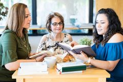 Group of women at book club. Beautiful latin women friends reading books at book club Stock Photos