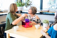 Woman receiving a present from friends at cafe. Beautiful latin women giving present to her best friend while sitting in a coffee shop Royalty Free Stock Photo
