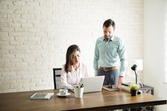 Latin man supervising his colleague Royalty Free Stock Images