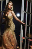 Beautiful latina lush breasts in a yellow dress and a magnificent crown on his head, opens the glass door. Beautiful latina lush breasts in a yellow dress and a royalty free stock photography