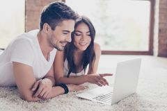 Beautiful latino mulatto lovers are browsing info on laptop and royalty free stock photography