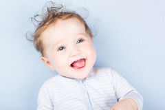 Beautiful laughing baby on a blue blanket Royalty Free Stock Image