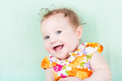 Beautiful laughing baby girl in a colorful floral dress Royalty Free Stock Images