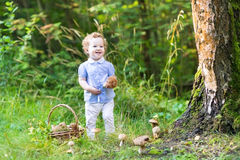 Beautiful laughing baby girl having fun gathering mushrooms Royalty Free Stock Photography