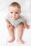 Beautiful laughing baby sitting on bed. Beautiful laughing baby sitting on white bed Royalty Free Stock Photography