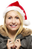Beautiful laughing blonde woman in a parka wearing. Santa's hat on white background Stock Photos