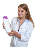 Beautiful laughing female seller presents new lotion Royalty Free Stock Photography