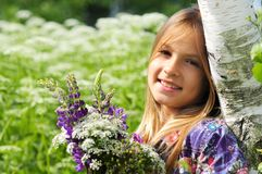 Beautiful laughing girl in a field of purple lupine flowers. Stock Photo