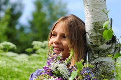 Beautiful laughing girl in a field of purple lupine flowers. Royalty Free Stock Images