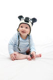 Beautiful laughing happy baby boy sitting on white bed in knitte. D hat Stock Image