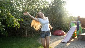 Beautiful laughing young woman enjoying warm summer rain in backyard garden. Beautiful laughing woman enjoying warm summer rain in backyard garden stock video footage