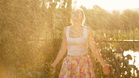 Beautiful laughing woman having fun under sparkling water from garden hosepipe at sunset. Laughing woman having fun under sparkling water from garden hosepipe at stock video