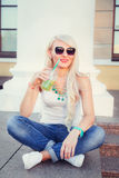 Beautiful laughing young woman in sunglasses sitting and drinkin Stock Image