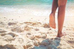 Beautiful leg of sexy women tan. Leisure in summer - Beautiful leg of sexy women tan. relax on sandy tropical beach. vintage color styles Royalty Free Stock Photography