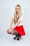 Beautiful leggy blonde posing on a gray background Royalty Free Stock Photography