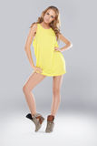 Beautiful leggy fashion model. With long curly blonde hair posing in a skimpy yellow miniskirt and boots, studio full body portrait Royalty Free Stock Photography