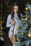 A beautiful, leggy, smiling girl, dressed in a sweater, panties and leggings, adorns the Christmas tree with garlands, light bulbs stock images