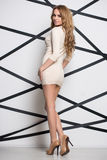 Beautiful leggy woman. Posing in beige short dress Royalty Free Stock Photography