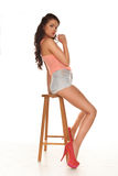 Beautiful leggy woman in stilettos. And sexy skimpy shorts posing sitting sideways on a wooden bar stool giving the camera a sultry seductive look, isolated on Royalty Free Stock Images