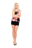 Beautiful leggy young blonde in black miniskirt. Isolated Royalty Free Stock Image