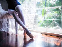 Beautiful legs of ballet dancer sitting on the chair and putting on her pointe shoes
