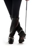 Beautiful legs in black leather horseman boots with riding-crop. Over white Royalty Free Stock Photos
