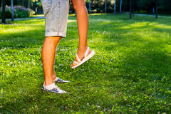 Beautiful legs of boy and girl. Love games. A date in the evening park. A date after work. Couple in love. Beautiful legs of boy and girl Stock Images