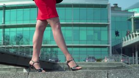 Beautiful legs of businesswoman in red dress. The woman in black shoes on heels is walking at the business center background. Camera in motion. Prores codec stock video footage
