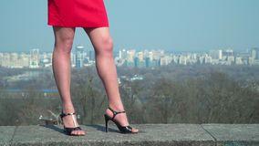 Woman in red skirt and in shoes on heels stand at blurred city background. Beautiful legs of businesswoman in red dress. The woman in black shoes on heels is stock video
