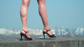 Thin female legs wearing shoes on heels is walking at blurred city background. Beautiful legs of businesswoman. The woman in black shoes on heels is walking at stock footage