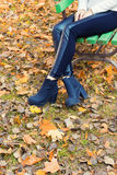 Beautiful legs girl  in black pants and boots sitting on the bench in autumn Park Stock Images