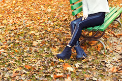 Beautiful legs girl in black pants and boots sitting on the bench in autumn Park Royalty Free Stock Photo