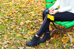 Beautiful legs girl in black pants and boots with yellow leaves in the hands of sitting on the bench in autumn Park Stock Images