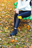 Beautiful legs girl in black pants and boots with yellow leaves in the hands of sitting on the bench in autumn Park Royalty Free Stock Image