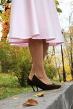Beautiful legs in a pink skirt royalty free stock image