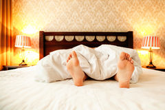 Beautiful legs in sexy lingerie lies on a bed Royalty Free Stock Images