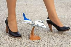 Beautiful legs stewardess and a model airplane stock image