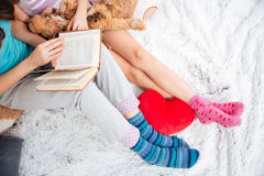 Beautiful legs of two women sitting and reading a book Stock Photos