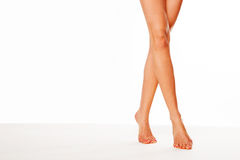 Beautiful legs walking on tip toe. Cropped view image of a pair of beautiful tanned female legs walking elegantly on tip toe over white with copyspace royalty free stock photography