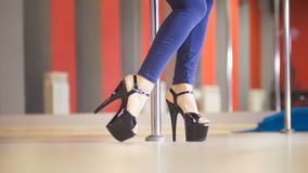 Beautiful legs of woman in black high-heeled shoes dancing on a pole in a studio. Close up royalty free stock photo