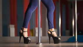 Beautiful legs of woman in black high-heeled shoes dancing on a pole in a studio. Close up royalty free stock photography