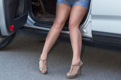 Beautiful legs of woman sitting in car with opened door Stock Photo