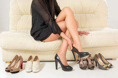 Beautiful legs. Woman trying many shoes. Choosing. Sitting on the white sofa. Shopping royalty free stock photo
