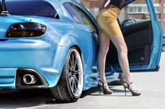 Beautiful legs of a woman who comes out of the sport car Royalty Free Stock Photography