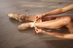 Beautiful legs of young ballerina who puts on pointe shoes sitting on wooden floor, top view with copy space. Ballet practice. Bea. Portrait of a professional Stock Photo