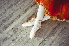 Feet in Pointe shoes on the floor. Beautiful legs of young ballerina who puts on pointe shoes at white wooden floor background, top view from above with copy royalty free stock photos