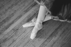 Feet in Pointe shoes on the floor. Beautiful legs of young ballerina who puts on pointe shoes at white wooden floor background, top view from above with copy stock photography
