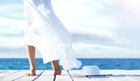 Beautiful legs of a young woman in white skirt on a wooden pier royalty free stock photo