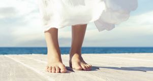 Beautiful and healthy feet of a young girl in white dress on a wooden pier. Vacation, resort and traveling concept. Royalty Free Stock Image